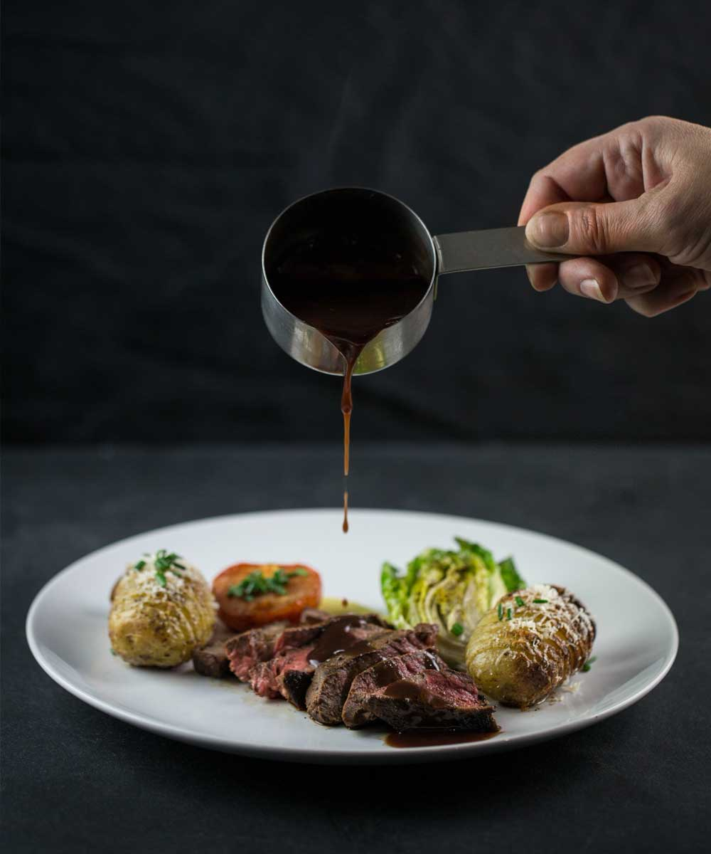 Pouring gravy over steak for wedding catering