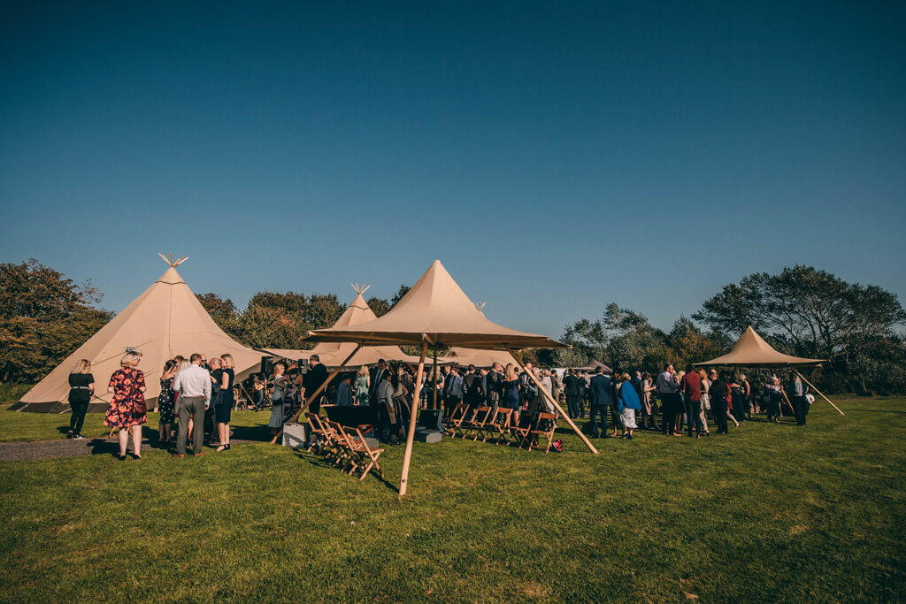 Guests outside tipis at a wedding